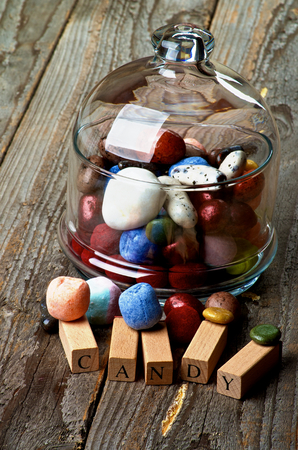 Various Colored Gum and Hard Candies in Glass Jar with Lid and Wooden Letters closeup on Rustic Wooden background photo
