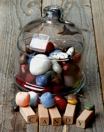 Delicious Colored Gum and Hard Candies in Glass Jar with Lid and Wooden Letters closeup on Rustic Wooden background photo