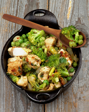 green pea: Tasty Homemade Chicken Stew with Broccoli, Bell Pepper and Green Pea in Black Saucepan with Wooden Spoon isolated on Rustic Wooden background. Top View Stock Photo
