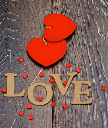 Two Red Hearts and Cardboard Word Love closeup on Dark Wooden background photo