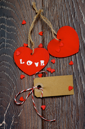 Two Red Hearts with Word Love, Blank Gift Card and Small Hearts closeup on Dark Wooden background photo