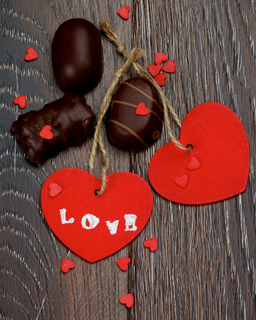 Two Red Hearts with Word Love, Chocolate Candies and Small Hearts closeup on Dark Wooden background photo