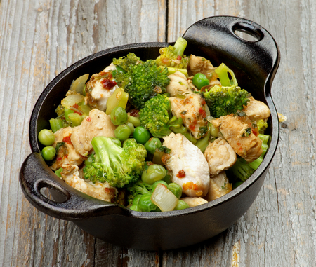 green pea: Delicious Homemade Chicken Stew with Green Pea, Broccoli and Bell Pepper in Black Saucepan isolated on Rustic Wooden background