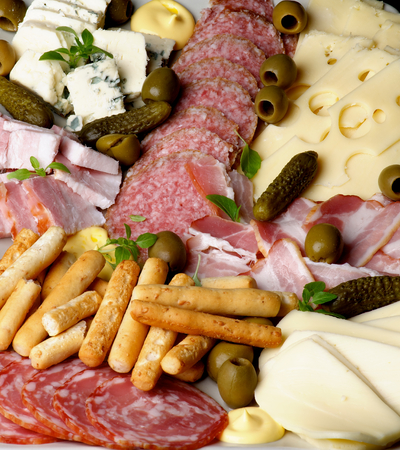 Background of Various Delicious Cheeses, Smoked Meat and Smoked Salami with Gherkins,Green Olives and Bread Sticks closeup photo