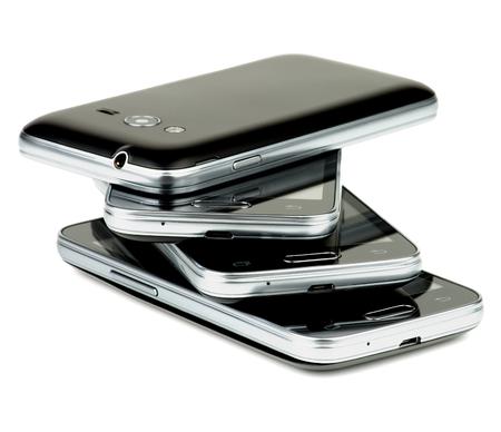 Stack of Contemporary Smartphones negros con detalles de plata aislado en el fondo blanco Foto de archivo