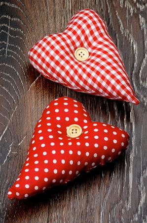 Two Handmade Textile Valentine Red Polka Dot Hearts closeup on Dark Wooden background photo