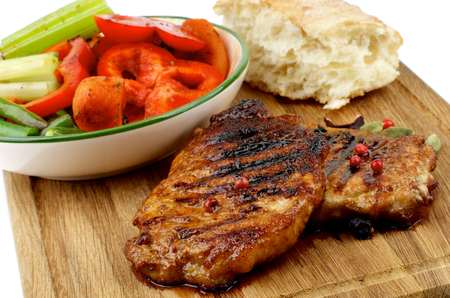 flap: Delicious Roasted Pork Steaks with Vegetable Stocks and Flap of Bread on Wooden Cutting Board isolated on white background. Focus on Steaks