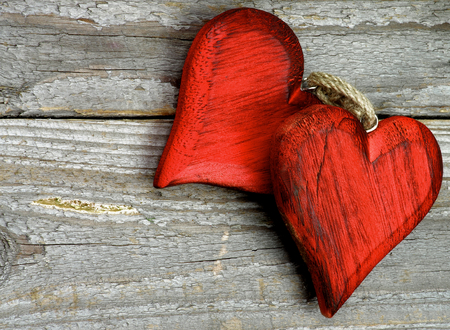 Pair of Handmade Wooden Red Hearts isolated on Rustic Wooden background. Top View photo