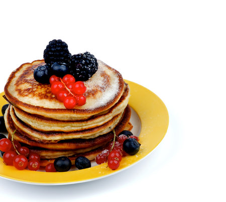 pancake week: Yellow Plate with Stack of Delicious Pancakes with Red Currant, Blackberry, Blueberry and Sugar Powder isolated on white background