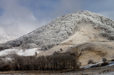 ridges: Mount Beshtau Ridges and Hills with Snowy Trees on Cloudy Sky background Outdoors