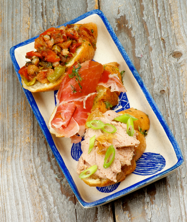cured ham: Delicious Tapas Bruschetta with Pate, Spring Onion, Cured Ham, Bacon andVegetables on Garlic Bread on Plate isolated on Rustic Wooden background. Top View