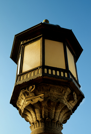 street lantern: Obsolete Decorative Street Lantern with Forging Details on Blue Sky background Outdoors Stock Photo