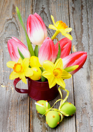 Bunch with Yellow Daffodils and Magenta Tulips in Watering Can with Colored Easter Eggs closeup on Wooden background photo