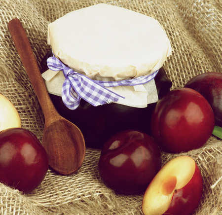 Jar of Plum Jam with Wooden Spoon, Ripe Purple Plums Full Body and Halves closeup on Wicker Sackcloth background Stock Photo