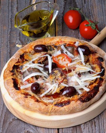 queso rayado: Pizza casera con tomates, aceitunas rojas y queso rallado sobre C�rculo de corte Junta sobre fondo de madera