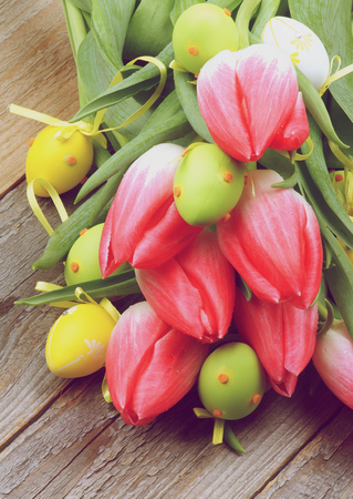 retro styled: Arrangement of Bunch Magenta Tulips with Yellow and Green Spotted Easter Eggs closeup on Wooden background. Retro Styled