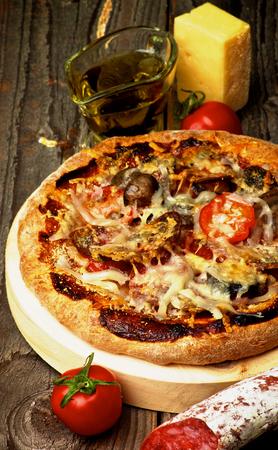 queso rallado: Pizza casera con tomate, salami y queso rallado sobre el Circle Tabla de cortar e ingredientes en el fondo de madera. Enfoque en primer plano