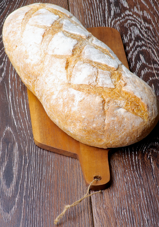 Big Loaf of White Wheat Bread Full Body on Wooden Cutting Board closeup on Hardwood background photo