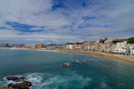 blue facades sky: Coastline and View on Apartment Buildings and House Facades on Cloudy Blue Sky background, Blanes, Spain