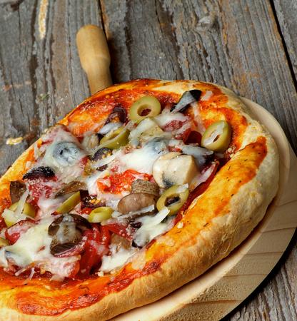 queso rayado: Pizza hecha en casa con las setas comestibles, tomates, aceitunas verdes, Embutidos y queso rallado sobre C�rculo de corte Junta de detalle sobre fondo de madera r�stica Foto de archivo