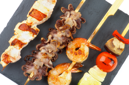 wooden stick: Grilled Salmon, Octopuses, Shrimps and Vegetables on Wooden Stick closeup Black Stone Plate. Top View