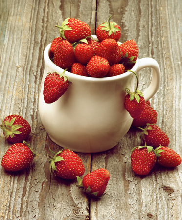 Heap of Fresh Ripe Forest Strawberries in White Bowl closeup on Rustic Wooden background. Retro Styled photo