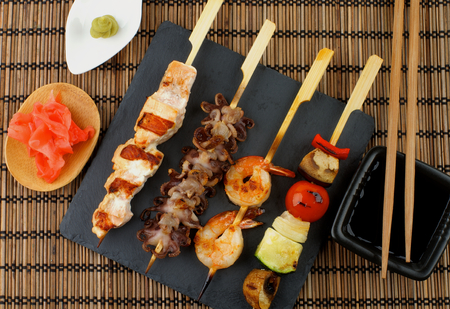 wooden stick: Grilled Salmon, Octopuses, Shrimps and Vegetables on Wooden Stick with Ginger, Soy Sauce and Wasabi on Straw Mat . Top View