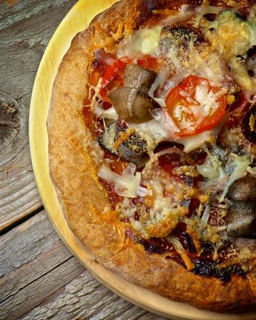 queso rallado: Pizza hecha en casa con setas del bosque, tomates y queso rallado Corte transversal sobre Círculo de corte Junta sobre madera. Vista Superior