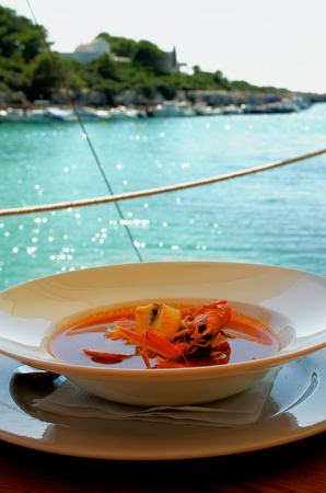 whitefish: Stewed Bouillabaisse Soup with Delicious Seafood closeup in White Bowl on Blurred Sea Harbor background Outdoors
