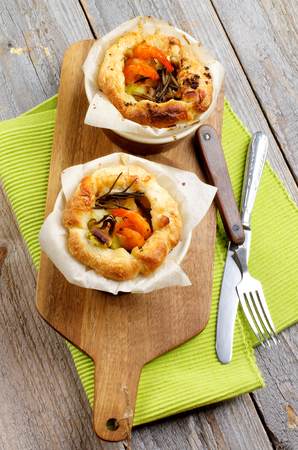 ovenbaked: Delicious Puff Pastry Snacks with Shrimps Leek and Cheese OvenBaked in Ramekin on Wooden Cutting Board with Fork and Knife Stock Photo