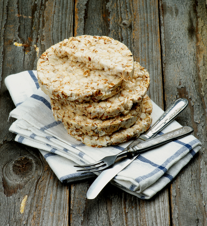 galettes: Stack of Puffed Spelt Oat Galettes with Silverware Fork and Knife on Checkered Napkin closeup on Rustic Wooden background. Health Eating Concept Stock Photo