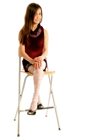 sit down: Attractive Teen Girl with Long Brown Hair in Purple Dress Sitting on Chair and Posing isolated on white background