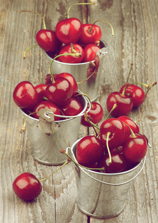 retro styled: Ripe Sweet Cherries in Three Tin Buckets isolated on Rustic Wooden background. Retro Styled