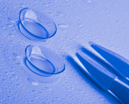 ultramarine: Arrangement of Two Contact Lenses with Water Droplets and Special Tweezers isolated on Wet background. Ultramarine Toned