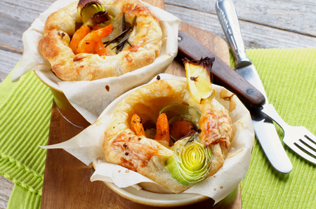 ovenbaked: Two Ramekins with Puff Pastry Snacks with Shrimps, Leek and Cheese Oven-Baked on Wooden Cutting Board with Fork and Knife