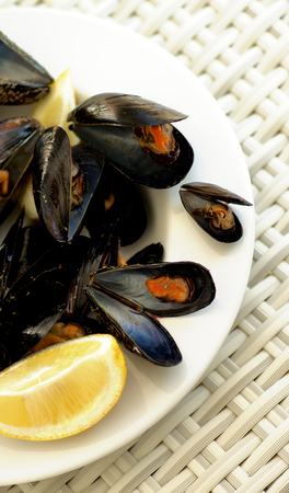 prepared shellfish: Arrangement of Boiled Mussels with Lemon on White Plate closeup on Wicker background. Top View