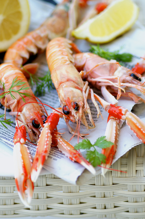 prepared shellfish: Delicious Grilled Langoustines with Lemon and Parsley on Newspaper closeup on Wicker background. Focus on Animal Eyes Stock Photo