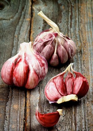lobule: Fresh Raw Pink Garlic Full Body and Lobule closeup on Rustic Wooden background Stock Photo