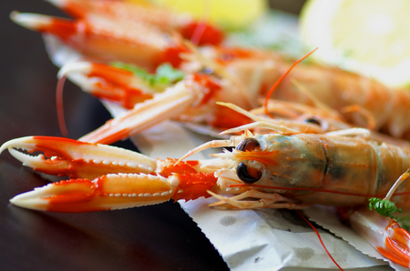 prepared shellfish: Delicious Grilled Langoustines  on Newspaper closeup on Dark Wooden background. Focus on Animal Eyes Stock Photo