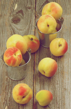 styled: Fresh Ripe Apricots in Tin Buckets closeup on Rustic Wooden background. Retro Styled Stock Photo