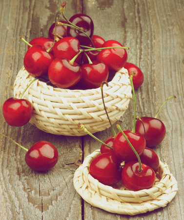 retro styled: Two Wicker Bowls with Ripe Sweet Cherries isolated on Rustic Wooden background. Retro Styled