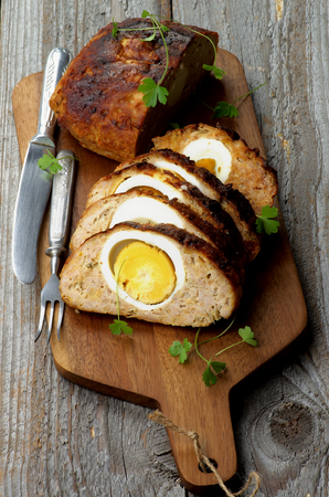 Delicious Homemade Meatloaf Stuffed with Boiled Eggs on Cutting Board with Knife and Fork closeup on Rustic Wooden background