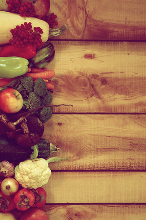 retro styled: Frame of Various New Harvest Vegetables, Fruits, Roots, Edible Mushrooms and Berries closeup on Wooden background. Retro Styled