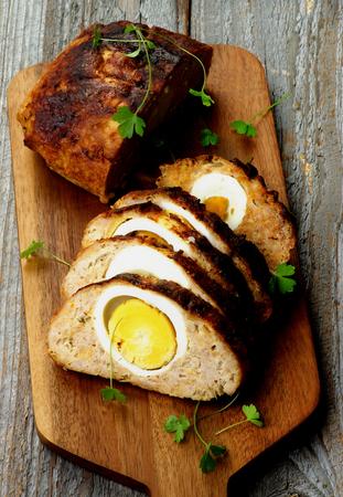 pastel de carne: Delicioso pastel de carne hecha en casa relleno con huevos duros en la tarjeta de corte de detalle sobre fondo de madera rústica Foto de archivo