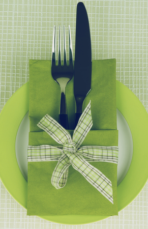 table knife: Elegant Table Setting with Fork and Table Knife into Green Napkin Decorated with Checkered Bow on Plate. Retro Styled Stock Photo