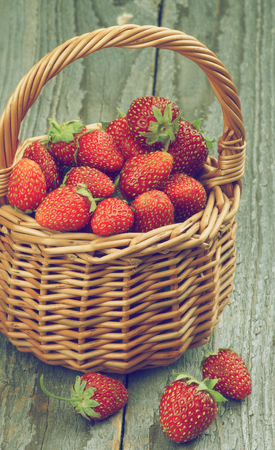 retro styled: Fresh Ripe Forest Strawberries in Wicker Basket isolated on Rustic Wooden background. Retro Styled Stock Photo