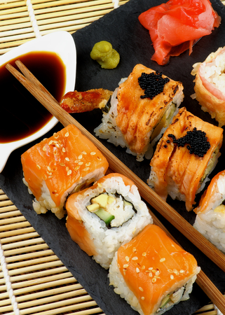 straw mat: Arrangement of Various Maki Sushi with Smoked Salmon, Eel and Tempura Crab on Stone Plate with Ginger, Soy Sauce and Wasabi closeup on Straw Mat background