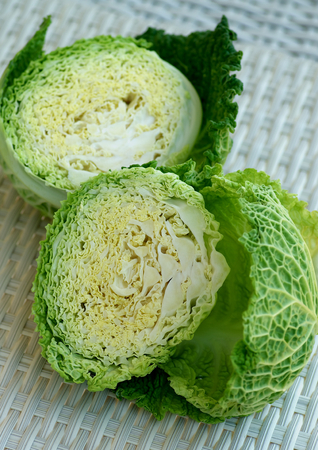 savoy cabbage: Halves of Green Leafy Texture Savoy Cabbage closeup on Wicker background