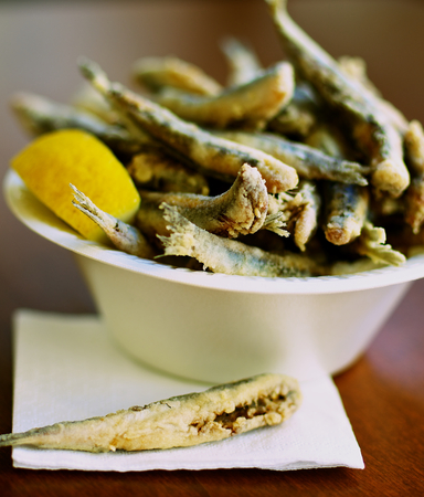 smelt: Delicious Deep Fried Small Fish in Bowl with Lemon. Focus on One Fish on Foreground Stock Photo