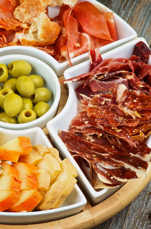 cured ham: Arrangement of Spanish Snacks with Various Cheeses, Jamon, Cured Ham and Green Olives on Serving Plate closeup on Wooden background